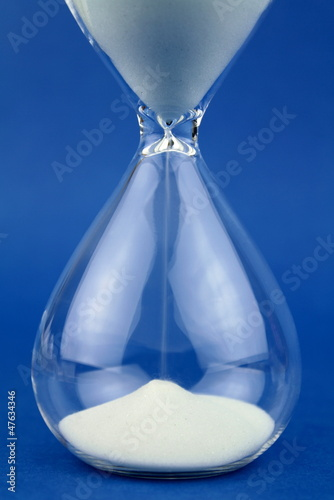 Close up hourglass on blue background.