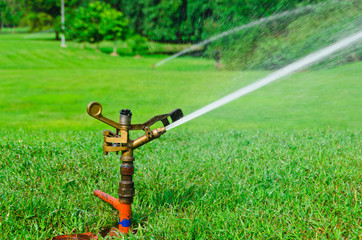 A metal automatic water sprinkler in the field