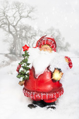 Father Christmas with glowing lantern in snowy winter scene