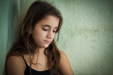 Depressed girl with a sad expression next to a dirty wall