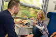 Couple eating sandwiches on train traveling smile