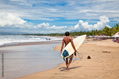 Young man with surf board on beach in Bali, Indonesia.