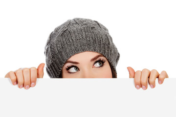 Girl in knitted hat looking over white board