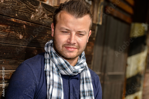 Pensive attractive man leaning against wooden wall