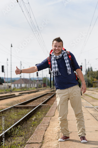Man hitchhiking on railroad train station smiling