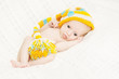 Newborn baby close up in woolen hat over white soft background.