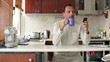 Man drinking tea and using smartphone in kitchen
