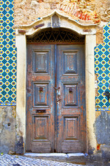 Old wooden door in Portugal. Wall of  tiles