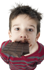 Smiling little boy eating chocolate