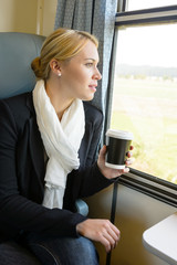 Woman looking out the train window pensive