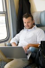 Man sitting in train using laptop computer