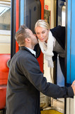 Man kissing woman goodbye on cheek train
