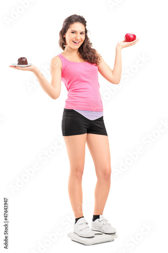 Smiling female on a weight scale holding a red apple and cake
