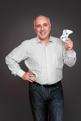 excited senior man holding joystick