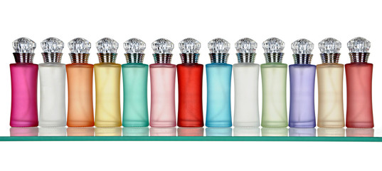 Glass bottles of perfume in a row on glass shelf
