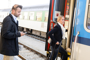 Woman getting on train man texting phone