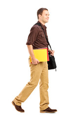 Male student with shoulder bag holding books and walking