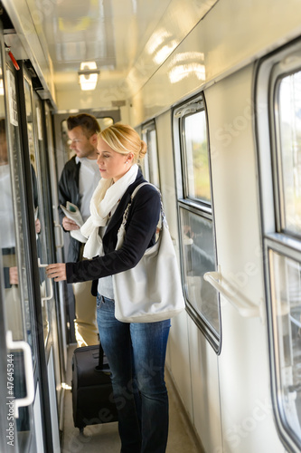 Woman opening the  door of train compartment
