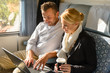 Woman and man relaxing in train laptop