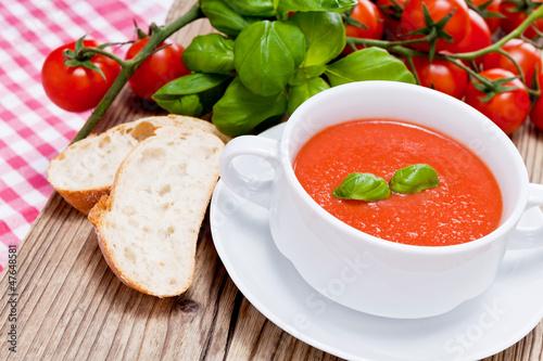 Leinwanddruck Bild Frische tomatensuppe in einer weißen suppentasse mit basilikum