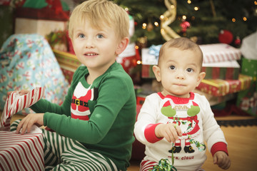 Baby and Young Boy Enjoying Christmas Morning Near The Tree