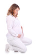 Smiling pregnant woman in white squats on haunches