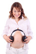 Pregnant woman in white holds headphones close to belly isolated