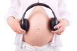 Hands of pregnant woman holding headphones close to belly