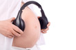 Hands of pregnant woman in white holding black headphones