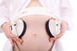Hands of pregnant woman in white holding white headphones
