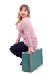 Young beautiful woman in pink blouse sits on suitcase and looks
