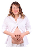 Pregnant woman in white depicts heart by hands on belly isolated