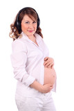 Pregnant woman in white listens to music on headphones