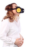 Pregnant suffering woman in white and respirator holds belly