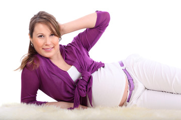 Pregnant woman lies on white fur isolated on white background.