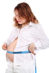 Pregnant woman in white measures stomach  by centimeter tape