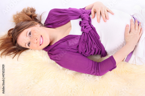 Beautiful young pregnant woman lies on white fur and smilies.