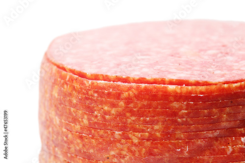 Close up of pink appetizing salami sausage pieces isolated