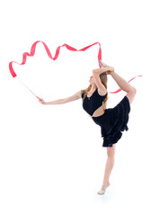 Gymnast in black dress with red ribbon stands on one leg