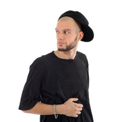 Rapper wearing black t-shirt and hat looks into distance