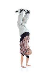 Breakdancer stands on two hands isolated on white background.