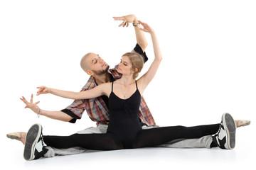 Ballerina in black and bald breakdancer sit on floor