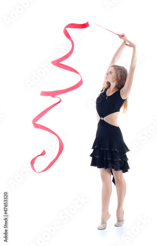 Young graceful gymnast in black dress with red ribbon