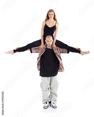 Breakdancer keeps on shoulders ballerina in black isolated