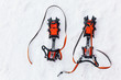 Pair of orange crampons with spikes for mountaineering