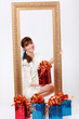 Happy girl holds box with gift and looks out from gilt frame