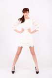 Beautiful young woman in white openwork dress holds by waist poster