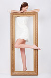 Beautiful young woman in white dress stands behind frame
