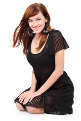 Beautiful girl in black dress and bid earrings sits on floor