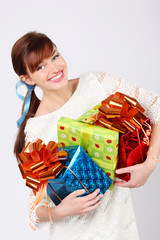 Smiling beautiful girl holds boxes with gift